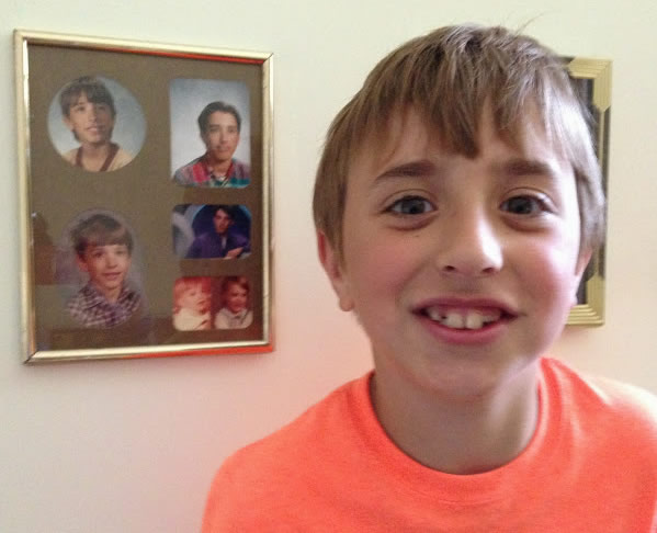 Here's Cam standing next to some photos of me at my grandma's house.